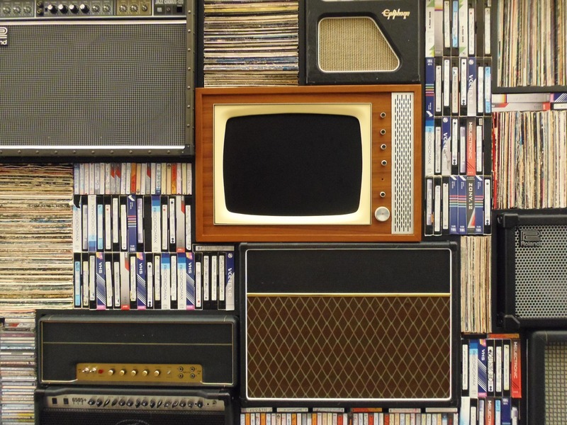 Antique TV surrounded by VHS tapes and LP records.